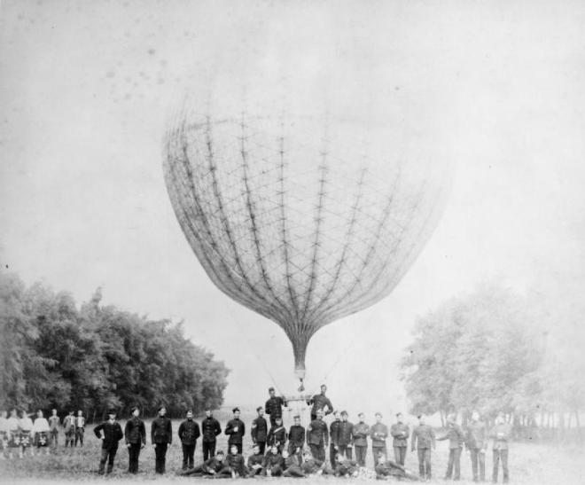 Soldiers of the Royal Engineers (balloon section) stood in front of the basket of a fully inflated observation balloon, some men in kilts are stood at the edge of the photograph. Image slightly overexposed.  © IWM (RAE-O 677